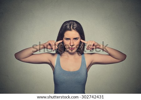 Closeup portrait young angry unhappy woman with closed ears looking at you annoyed by loud noise giving her headache ignoring isolated on gray wall background. Negative emotion perception attitude - stock photo