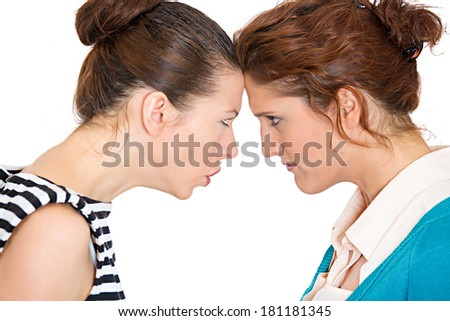 Closeup portrait young angry women, looking at each other with hatred, blaming for problem isolated white background. Friendship difficulties, problems at work, negative emotion expressions, feelings - stock photo