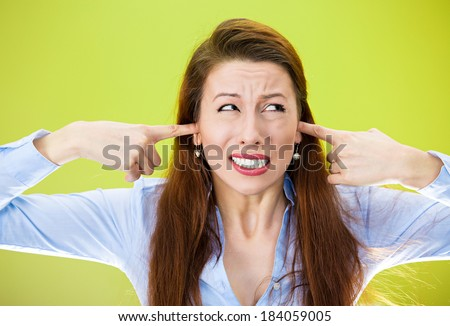 Closeup portrait, young annoyed, unhappy, stressed woman covering her ears, looking up, to say, stop making loud noise, giving me headache, isolated green background. Negative emotion, reaction. - stock photo