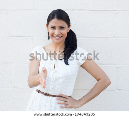 Closeup portrait, young, beautiful, smiling business woman, student, customer service agent giving you handshake, isolated white brick background. Positive human emotions, feelings, face expressions - stock photo