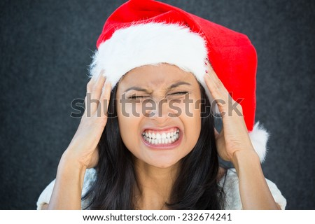 Closeup portrait, young beautiful worried stressed wife, mother, woman in santa claus hat with hands on temples about to break down, isolated gray black background. Last minute christmas shopping - stock photo
