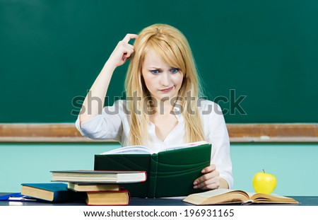 Closeup portrait young blonde woman, confused student scratching her heard sitting at desk in classroom thinking hard, reading book puzzled isolated background with chalkboard. Human facial expression - stock photo