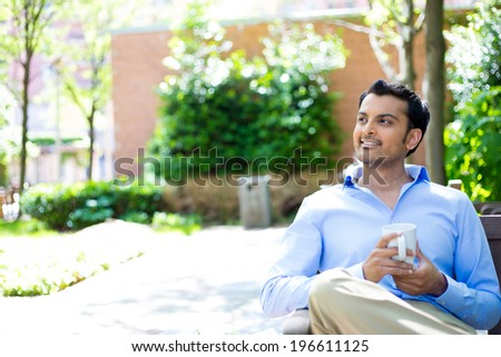 Closeup portrait, young business man drinking mug outside, sitting on wooden bench relaxing, daydreaming, isolated trees, building background - stock photo