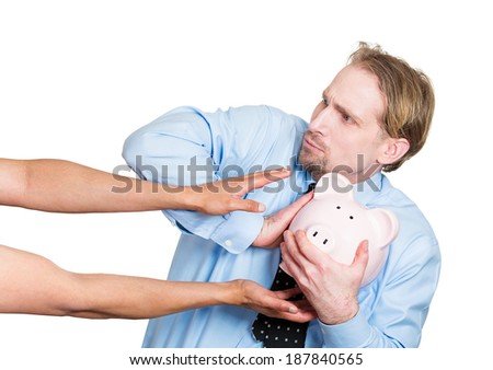 Closeup portrait young business man holding piggy bank, looking scared, angry, worried,  frustrated, trying to protect his savings from being stolen, isolated white background. Financial fraud robbery - stock photo