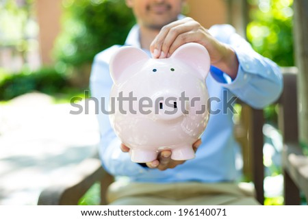 Closeup portrait, young business man putting coins in piggy bank, isolated outdoors trees background. Smart wise currency financial investment wealth decisions. Budget management and savings - stock photo