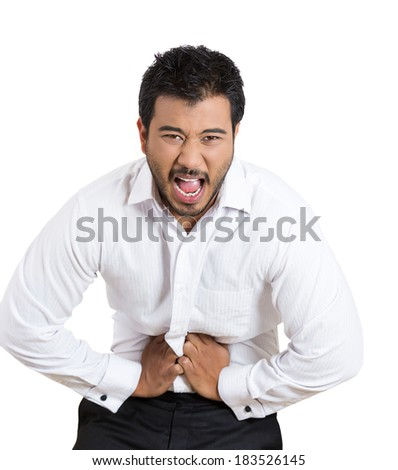 Closeup portrait, young business man, unhealthy, unwell corporate worker, doubling over in gastrointestinal stomach pain, isolated white background. Human emotions. Acute abdomen - stock photo