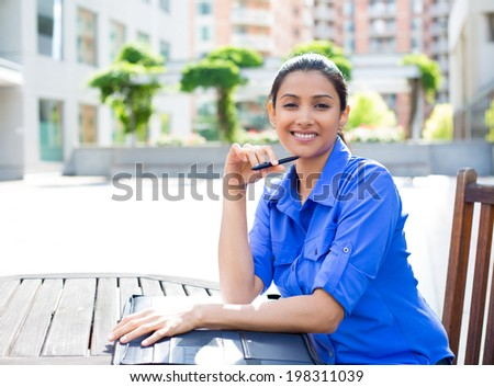 Closeup portrait, young business woman smiling, posing for camera, holding pen, sitting on wooden chair at table, isolated city background with buildings - stock photo