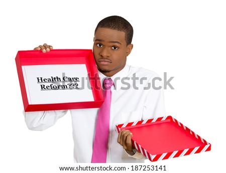 Closeup portrait, young confused skeptical man holding a sign health care reform in gift box, uncertain of universal insurance coverage, isolated white background. politics, government legislation - stock photo