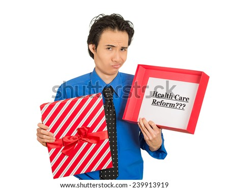 Closeup portrait, young confused skeptical man holding sign health care reform in gift box, uncertain of universal insurance coverage, isolated white background. Politics, government legislation - stock photo
