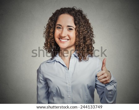 Closeup portrait young, curly brown hair woman student being excited giving showing thumbs up hand gesture isolated grey background. Positive human emotion face expression feeling sign symbol attitude - stock photo