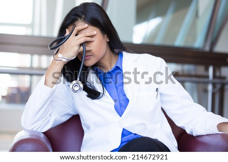 Closeup portrait, young depressed woman healthcare practitioner holding face in despair, isolated hospital background - stock photo