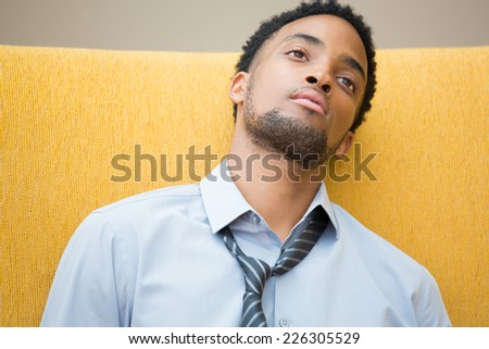 Closeup portrait, young disturbed, distressed employee in blue shirt striped tie, exhausted, resting head on seat, worried about something, about to collapse. Staring out in space  - stock photo