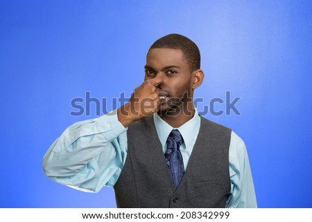 Closeup portrait young executive man, disgust on face, pinches his nose, something stinks, bad smell, situation isolated blue background. Negative emotion facial expression, perception body language - stock photo