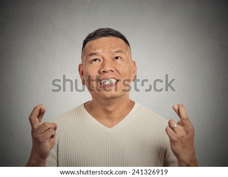 Closeup portrait young funny guy, middle aged man crossing fingers, wishing, hoping for best miracle isolated grey wall background. Positive human emotion face expression feeling attitude anticipation - stock photo
