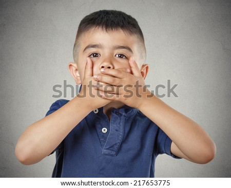 Closeup portrait young handsome man, boy closing, covering mouth with hands can't speak hiding isolated grey wall background. Speak no evil concept. Human emotion facial expression feeling reaction - stock photo