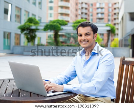 Closeup portrait, young handsome man in blue shirt typing away, browsing digital computer laptop, isolated background of sunny outdoor, green trees, office background
