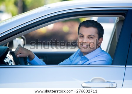 Closeup portrait, young handsome man in his new silver gray car, relaxing, hand on steering wheel, looking out window, isolated on outdoors background with vehicle. - stock photo
