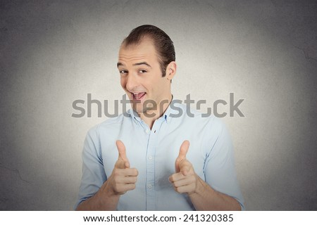 Closeup portrait  young handsome man with two hands guns sign gesture pointing at you camera, isolated grey wall background. Positive human emotion facial expression feelings, signs and symbols - stock photo