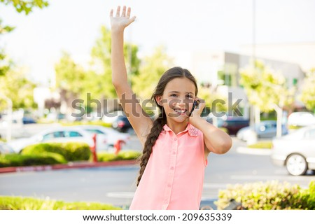 Closeup portrait, young happy child, girl talking on cell, smart phone, isolated outdoors background. Positive human emotions, facial expressions, life perception, communication - stock photo