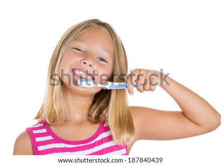 Closeup portrait young, happy, smiling girl brushing her teeth with toothpaste, manual toothbrush, isolated white background. Oral dental health, disease prevention. Positive face expression, emotion - stock photo