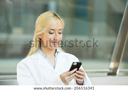 Closeup portrait young healthcare professional, doctor, nurse, dentist, researcher, physician assistant reading text sms, message on cellphone holding smart phone isolated hospital hallway background - stock photo