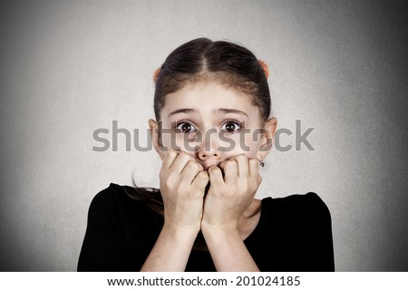 Closeup portrait young little girl biting her finger nails, looking at you with fear of something, anxious isolated  black background. Human facial expression, body language, reaction, life perception - stock photo