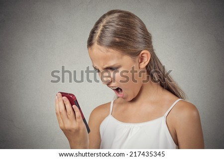 Closeup portrait young mad, frustrated angry teenager girl yelling while on phone isolated grey wall background. Negative human emotion facial expression feelings. Communication, conflict resolution - stock photo
