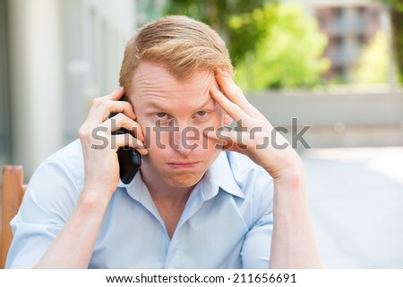 Closeup portrait, young man annoyed, frustrated, pissed off by someone listening on his mobile phone, bad news, isolated outdoors outside background. Long wait times, horrible conversations concept - stock photo
