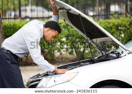 Closeup portrait, young man having trouble with his broken auto, opening hood trying to fix engine, isolated green trees outside background. Car won't start, dead battery - stock photo