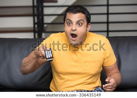 Closeup portrait, young man in yellow t-shirt, sitting on black leather couch, watching TV, holding remote, surprised at what he sees, mouth wide open, isolated indoors flat background - stock photo