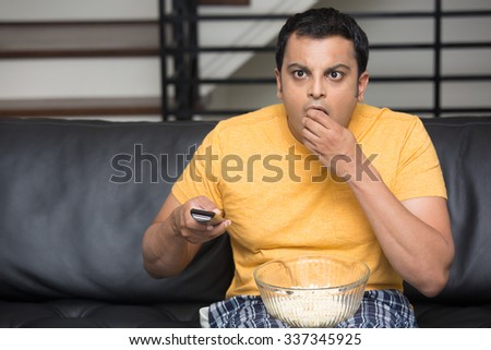 Closeup portrait, young man in yellow t-shirt, sitting on black leather couch, watching TV, holding remote, surprised at what he sees, munching popcorn, isolated indoors flat background - stock photo
