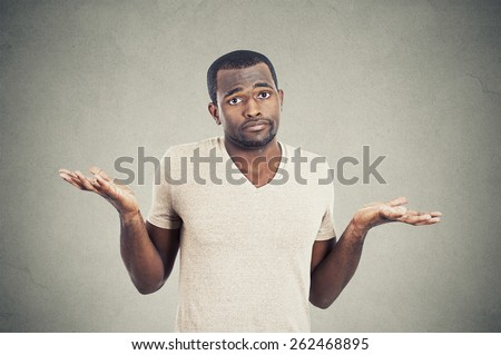 Closeup portrait young man shrugging shoulders who cares so what I don't know gesture isolated on grey wall background. Body language  - stock photo