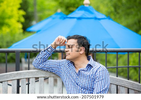 Closeup portrait, young man sitting on outside wooden bench, daydreaming about life, isolated outdoors green trees background - stock photo