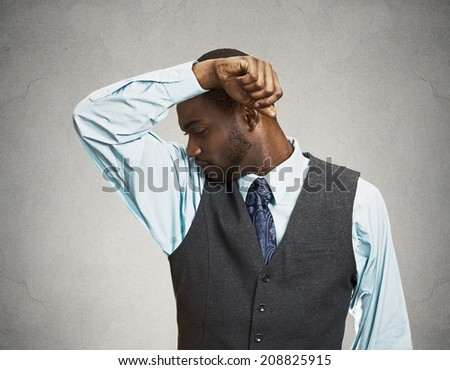 Closeup portrait young Man, Smelling sniffing Armpit, something Stinks very bad, foul Odor situation isolated grey, black background. Negative human emotions, facial expressions, feeling body language - stock photo