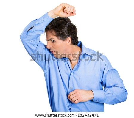 Closeup portrait young man, smelling, sniffing his wet armpit, something stinks, very bad, foul odor situation, isolated white background. Negative human emotions, facial expressions, feeling reaction - stock photo