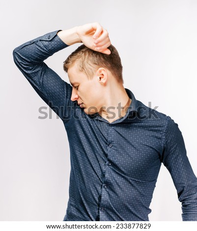 Closeup portrait young man, smelling, sniffing his wet armpit, something stinks, very bad, foul odor situation, isolated . Negative human emotions, facial expressions, feeling reaction - stock photo