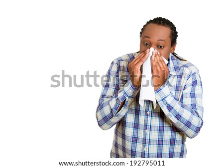 Closeup portrait young man, with allergy, cold, blowing his nose kleenex, looking miserable unwell very sick, isolated white background with copy space. Flu season, vaccination. Facial expressions - stock photo