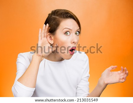 Closeup portrait young nosy woman hand to ear gesture trying carefully intently secretly listen in on juicy gossip conversation news privacy violation isolated orange background. Human face expression - stock photo