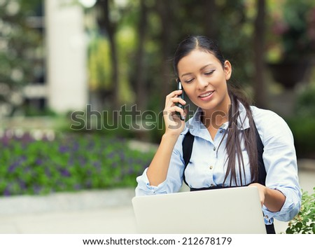 Closeup portrait, young pretty woman in blue shirt talking on phone, looking at computer laptop screen isolated background outdoor, green trees, office background. Positive emotions, face expressions - stock photo