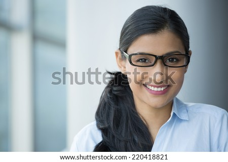 Closeup portrait, young professional, beautiful confident adult woman in blue shirt, with black glasses, smiling isolated indoors office background. Positive human emotions - stock photo