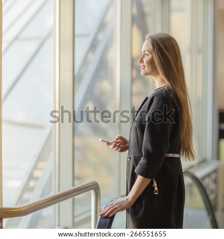 Closeup portrait, young professional, beautiful confident woman , friendly personality, smiling, looking outside glass window, isolated indoors office background. Positive human emotions - stock photo