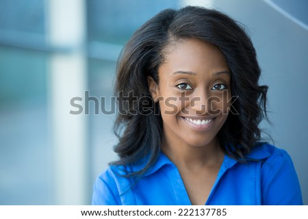 Closeup portrait, young professional, beautiful confident woman in blue shirt, friendly personality, smiling isolated indoors office background. Positive human emotions - stock photo