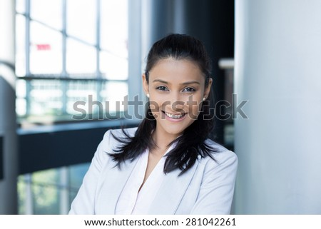 Closeup portrait, young professional, beautiful confident woman in gray white suit, friendly personality, smiling isolated indoors office background. Positive human emotions - stock photo