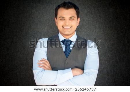 Closeup portrait, young professional, confident man in blue shirt, tie, gray vest, arms crossed folded, smiling isolated gray black background. Positive human emotions - stock photo