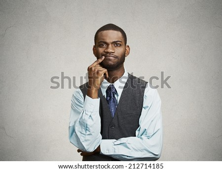 Closeup portrait young, puzzled business man thinking, deciding deeply something, finger on lips looking confused, unsure isolated grey wall background with texture. Emotion facial expression feeling - stock photo