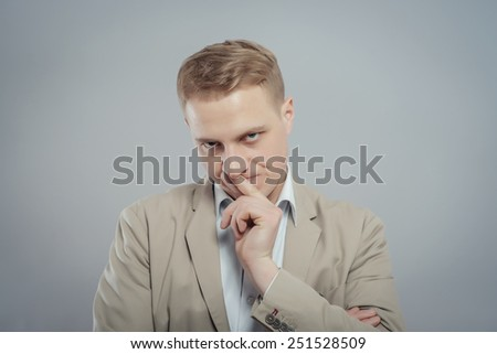 Closeup portrait young serious businessman placing finger on lips saying, shhh, be quiet, silence, isolated grey background. Facial expression, human emotions, sign, symbol, body language, perception - stock photo