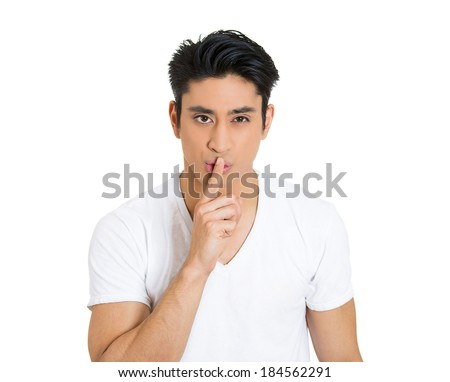 Closeup portrait, young serious man placing finger on lips as if to say, shh, be quiet, silence, isolated white background. Negative facial expression, human emotions sign, symbols, body language