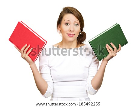 Closeup portrait young serious woman, confused student, holding red and green book in each hand, thinking hard, deciding which one to choose, way to go, isolated white background, clipping path