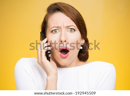 Closeup portrait young shocked business woman, corporate employee talking on cell phone, having unpleasant, bad conversation, isolated yellow background. Negative emotion, facial expressions, reaction - stock photo