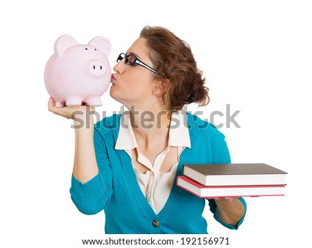 Closeup portrait, young, smiling student, happy woman, holding books in hand, kissing piggy bank, isolated white background. Value of higher education concept. College fund, money, tuition, savings - stock photo